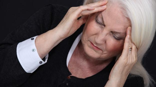 Eine Frau fasst sich besorgt und erschöpft an die Schläfen.