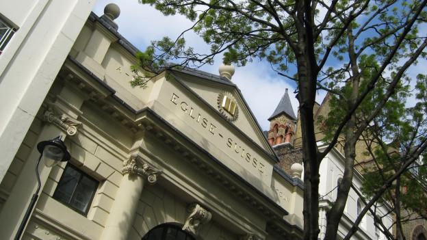 """Blick auf eine Hausfassade, auf der """"Eglise suisse"""" steht."""