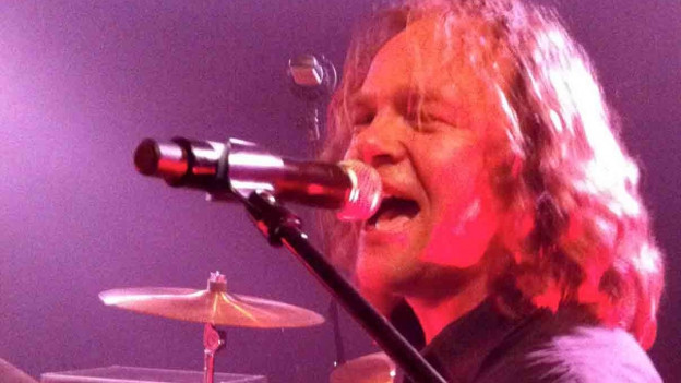 Mann am Mikrofon im Bühnenlicht.