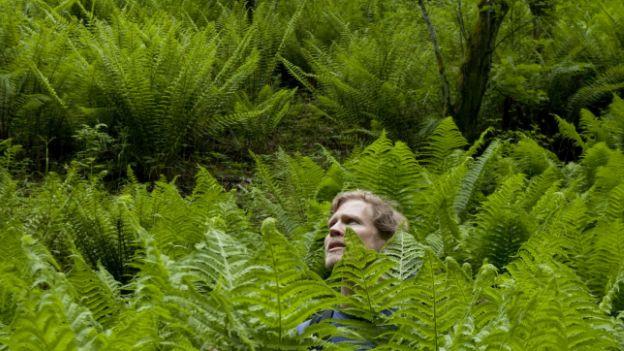 Jon Bollmann steht in einem Busch, der fast so gross ist wie er.