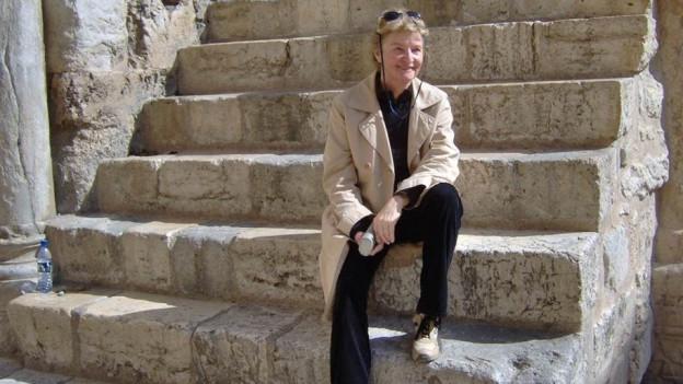 Eine Fru sitzt auf einer Steintreppe.