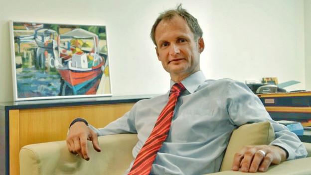 Philipp Stalder sitzt in einem Sessel, im Hintergrund ein Gemälde.