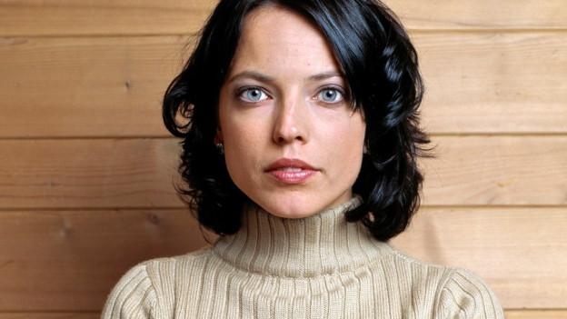 Eine Frau mit schwarzem Haar und grossen blauen Augen steht vor einer Holzwand.
