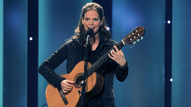 Eine Frau mit Gitarre steht vor einem Mikrofon.
