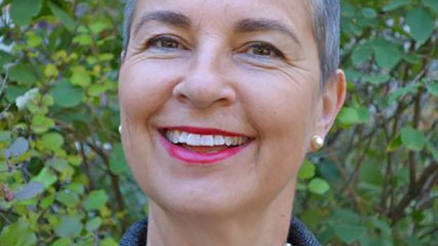 Eine lächelnde Frau mit kurzem grauen Haar