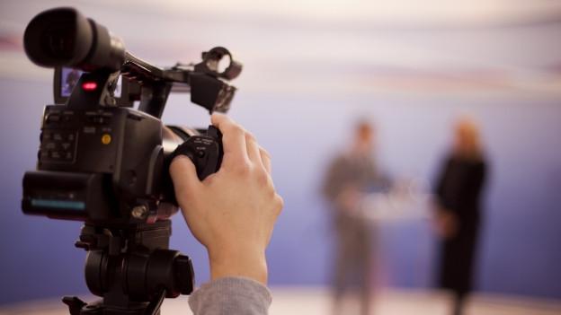 Symbolbild: Eine Hand bedient eine Kamera