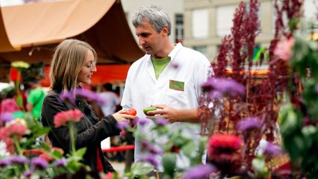 Béla Bartha (r.), Geschäftsführer der Stiftung Pro Specie Rara zeigt an einem Markt seltene Tomaten.
