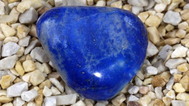 Symbolbild: Ein geschliffener Lapislazuli auf Kies.