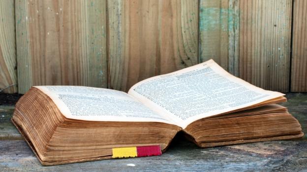 Alte Bibel liegt aufgeschlagen auf einem Tisch.