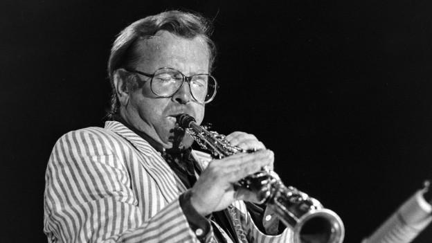 Schwarzweiss Foto von Klaus Doldinger bei einem Konzert. Er nspielt Klarinette.