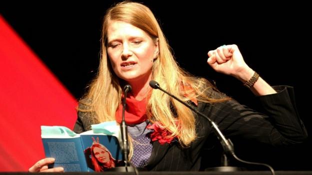 Eva Kurowski sitzt an einem Tisch während einer Lesung und liest aus ihrem Buch vor.