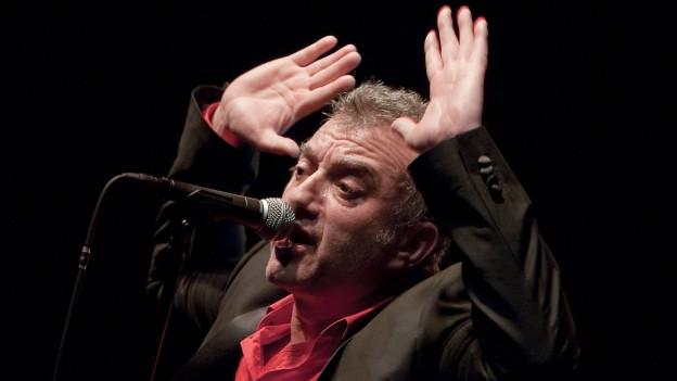 André Herzberg trägt einen schwarzen Anzug und ein rotes Hemd, ist ca. 50 Jahre alt und hält beide Handflächen hoch während er in ein Mikrofon singt.
