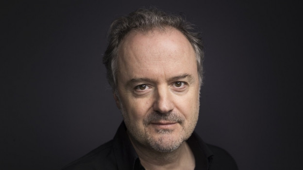 Porträt-Aufnahme eines Mannes mittleren Alters in einem schwarzen Hemd.