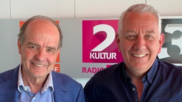 Zwei Männer mit grauen Haaren und blauen Hemden stehen vor der Kamera und lächeln. André Bechir ist links, Röbi Koller rechts.
