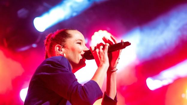Eine Frau steht auf einer Bühne. Sie hält sich ein Mikrophon an den Mund und lächelt. Viele Farben durch Scheinwerfer