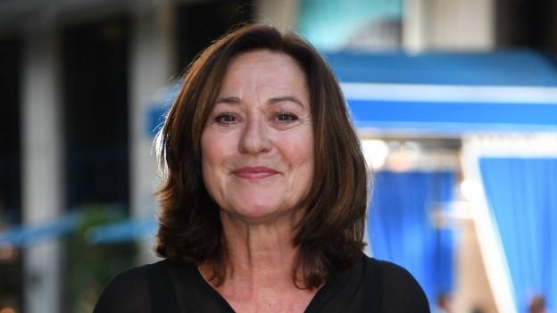 Frau mit dunklen Haaren lächelt in die Kamera