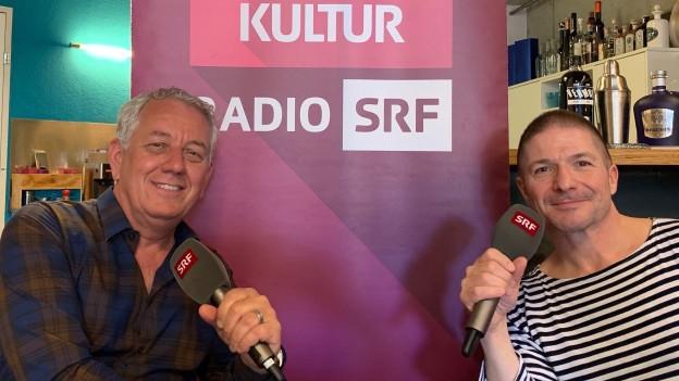 Zwei Männer sitzen vor einem SRF-Logo-Banner und halten ein Mikrophon in der Hand.