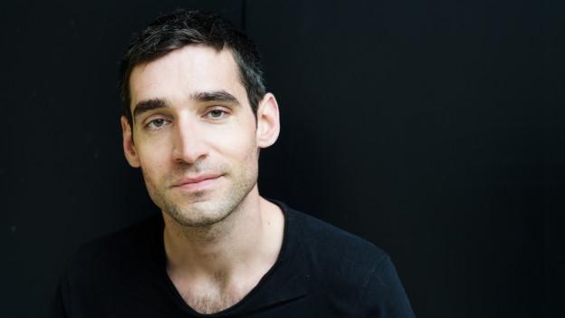 Mann mit kurzen Haaren vor schwarzem Hintergrund
