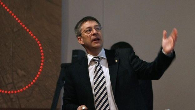 Mann in Anzug, rahmenloser Brille und Laserpointer in der Hand hebt seine Hand und zeigt auf eine nicht sichtbare Leinwand.