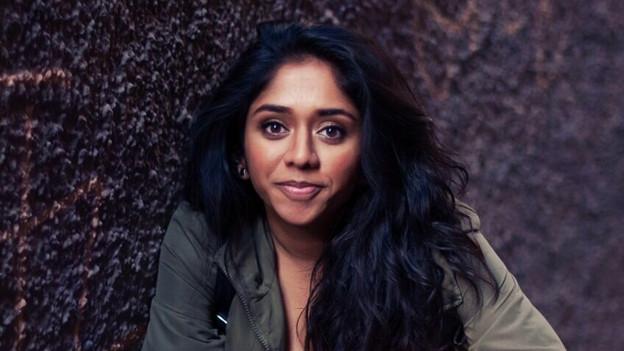 Frau mit dichten, langen, schwarzen Haaren steht vor einer dunklen Wand und lächelt in die Kamera.
