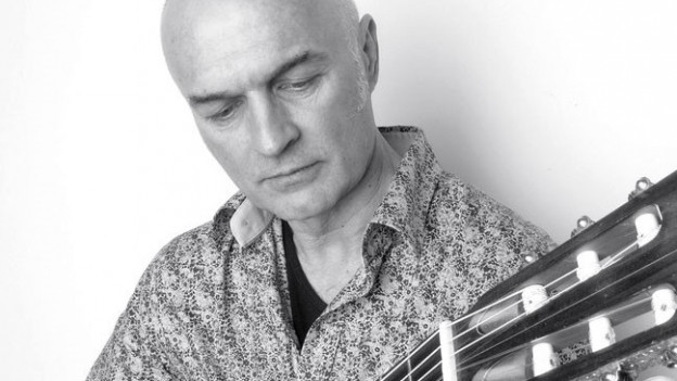 Ein Mann an einer Gitarre in schwarz-weiss