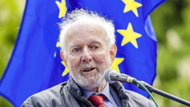 Ein grauhaariger Mann hinter einem Mikrofon und vor einer Flagge