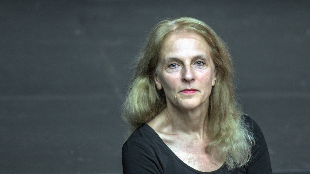 Eine Frau mit blonden langen Haaren blickt in die Kamera