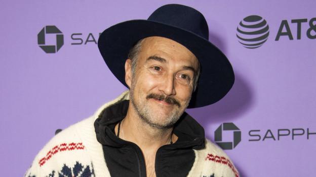 Mann mittleren Alters mit Hut, Schnauz und angegrautem Stoppelbart