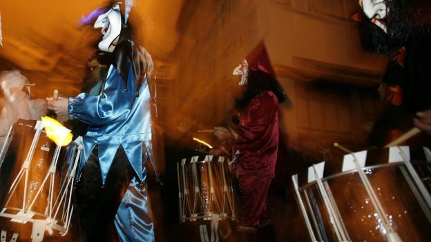 Verkleidete Menschen mit grossen Trommeln vor sich an der Basler Fasnacht