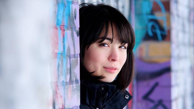 Um die 30-jährige Frau mit schwarzen, schulterlangen Haaren vor einer bunten Graffitiwand