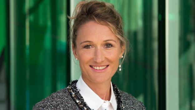 Frau mittleren Alters mit blonden Haaren vor grünem Hintergrund
