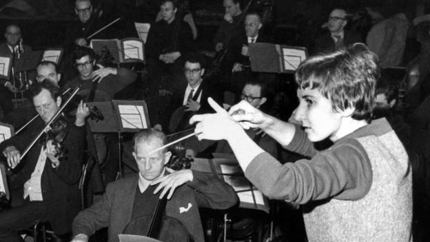 Frau dirigiert rein männliches Orchester - Aufnahme in Schwarzweiss