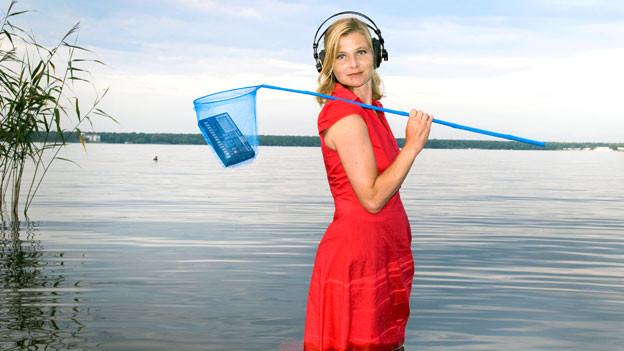 Bernadette La Hengst als Fischerin inszeniert – natürlich (?!) mit Kopfhörern.