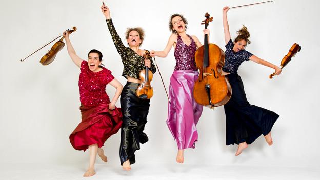 Vier Frauen mit Musikinstrumenten hüpfen.