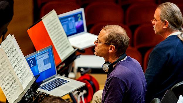 Zwei Musiker mit Notenblatt und Computer vor sich.