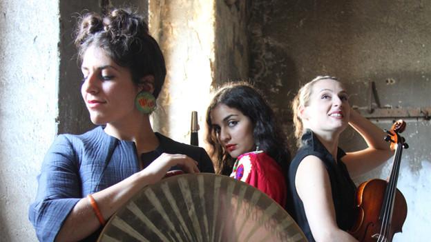Drei junge Frauen posieren mit Instrumenten