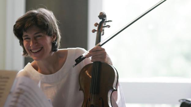 Kim Kakashian lacht mit einer Viola in der Hand.