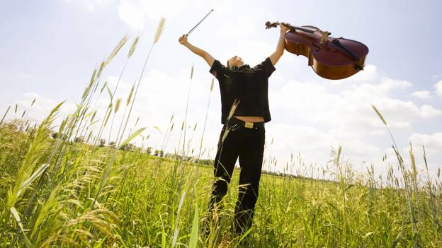 Ein Mann mit einem Cello in einem Feld.