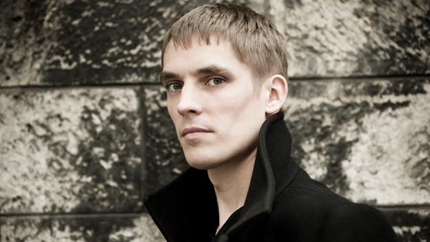 Cédric Tiberghien im Porträt. Er trägt einen schwarzen Mantel.