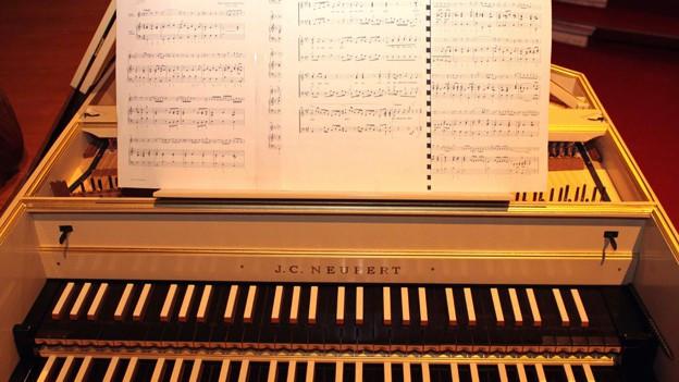 Cembalo von vorne mit Blick auf die Klaviatur und Noten.
