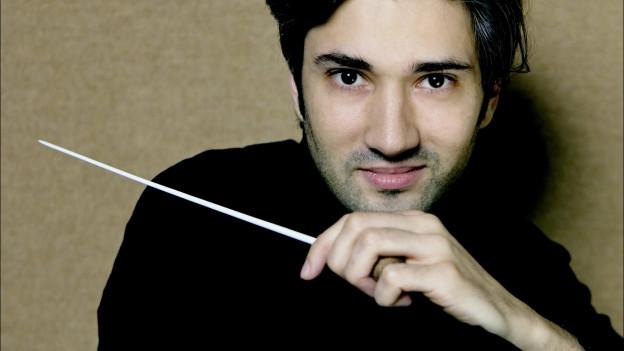 David Afkham hält einen Dirigentenstab.