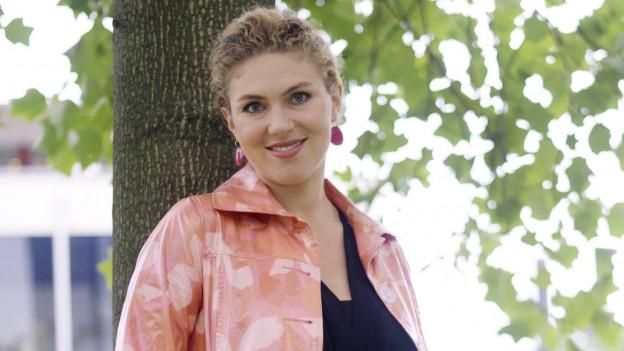 Annette Dasch steht vor einem Baum.
