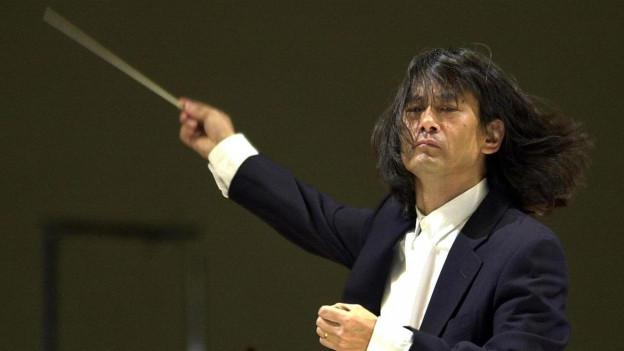 Dirigent Kent Nagano dirigiert mit wehendem Haar.
