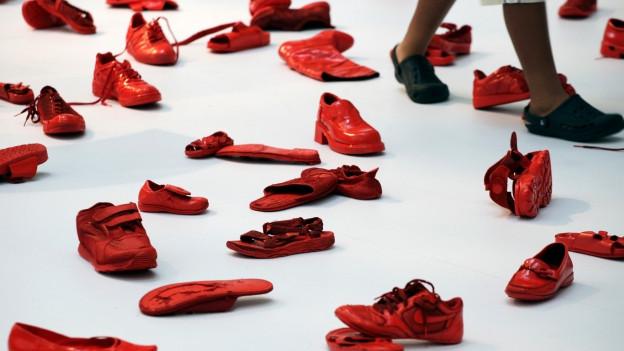 Viele rotgefärbte Schuhe liegen auf der Bühne.