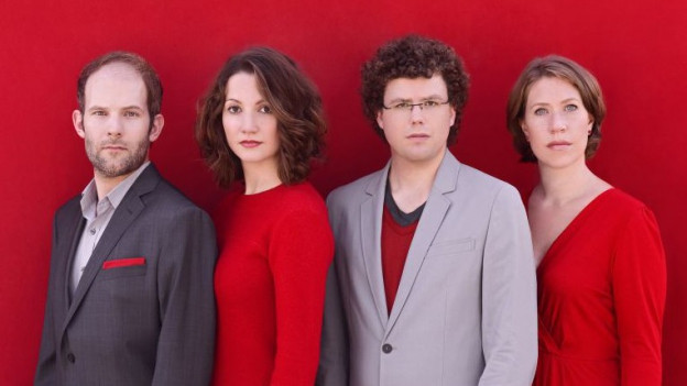 Zwei Frauen und zwei Männer stehen nebeneinander vor einem roten Hintergrund.