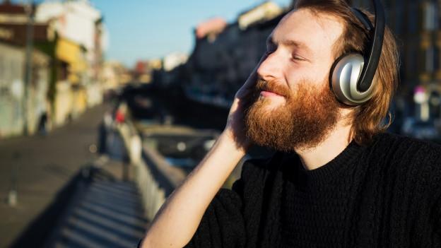 Mann hört Musik mit grossen Kopfhörern.