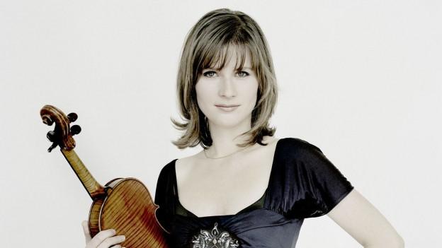 Eine Frau im dunklen Kleid mit Geige unter dem Arm.