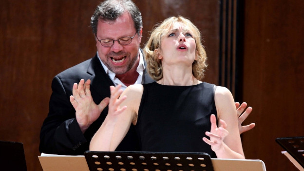 Ein Mann und eine Frau stehen gemeinsam hinter einem Notenständer und singen mit starker Gestik.