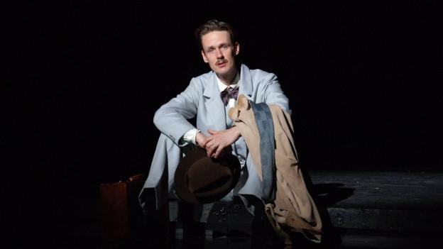 Ian Bostridge auf der Bühne in einer Rolle. Er ist chic gekleidet, sitzt auf dem Boden und weint.