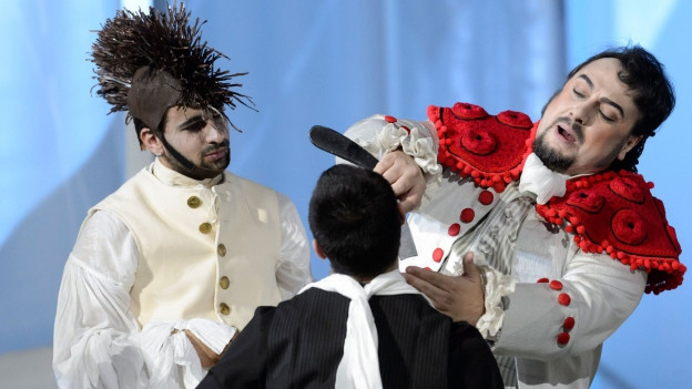Bühnenbild einer Oper: Zwei Männer stehen vor einem sitzenden Mann. Der eine rasiert ihn und singt dazu.